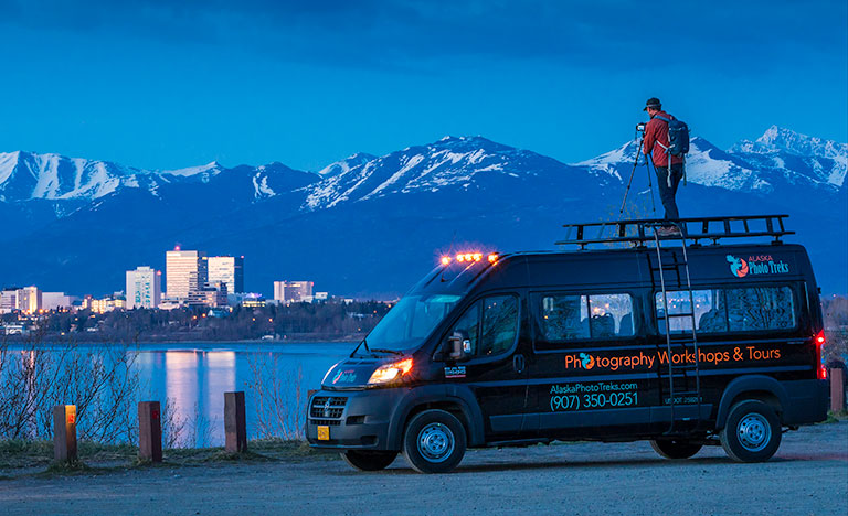 man photographing anchorage city skyline from top of van at twilight - anchorage photography guides