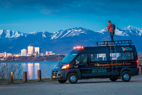 man photographing anchorage city skyline at twilight - anchorage photo tour