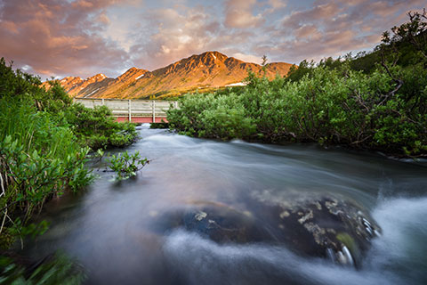 silky water flowing under a bridge in an alpine meadow at sunset - anchorage photo tour