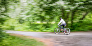 woman on bicycle in the rain with motion blur - all weather photography