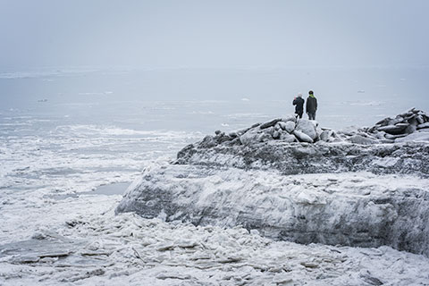 couple watching ice flows on turnagain arm - winter photo tour