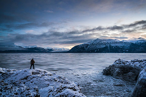 man photographing ice flows in turnagain arm at sunset - winter photo tour