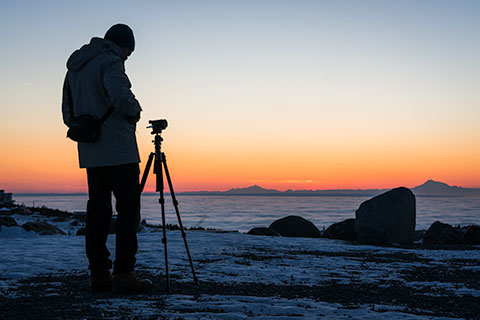 silhouette of photographer at sunset with tripod - winter photo tour