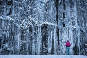 woman standing in front of frozen waterfall - winter photo tour