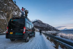 two photographers standing on van roof at sunset - winter photo tour