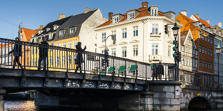 silhouettes of pedestrians on canal bridge in copenhagen - travel photography tips