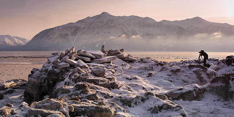 woman photographing ice flows in turnagain arm - photograph winter landscapes