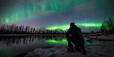 man kneeling with tripod while photographing auroras next to reflective water - photograph northern lights