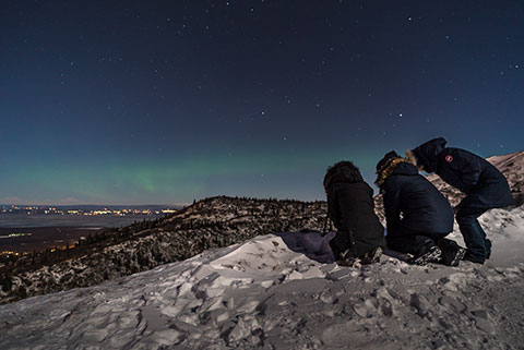 three people on mountainside looking at aurora arc - northern lights photo tour