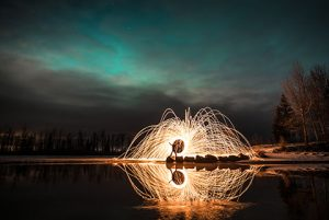 woman standing in circle of sparks from steel wool reflecting in water with aurora - northern lights photo tour