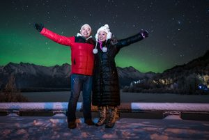 couple with arms up in front of auroras - northern lights photo tour