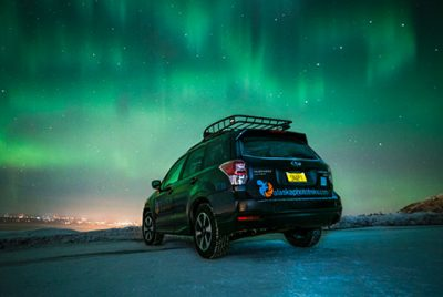subaru forester parked on mountain with auroras overhead - northern lights photo tour