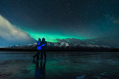 couple looking at aurora glow - northern lights photo tour