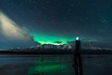 woman looking at aurora glow - northern lights photo tour