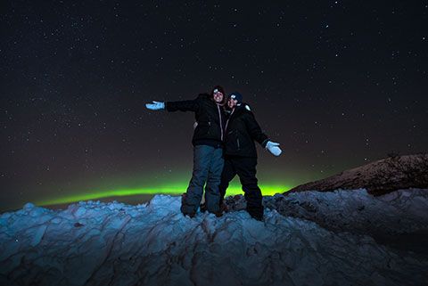 two girls with arms up on mountainside with aurora arc - northern lights photo tour