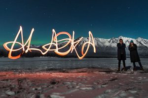couple standing by lightpainted word alaska - northern lights photo tour