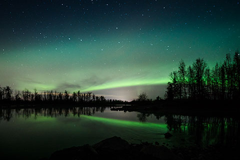 aurora arc reflecting in water - northern lights photo tour
