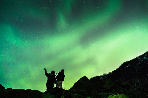 two women silhouetted against aurora - northern lights photo tour
