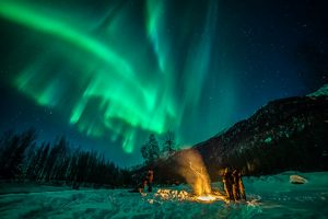 group of people standing around campfire with auroras overhead - northern lights photo tour