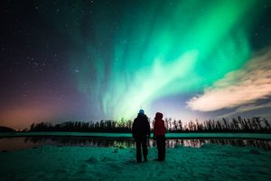 couple watching aurora by lake - northern lights photo tour