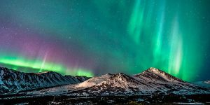 colorful auroras dancing over snow mountaintops - northern lights photo tour