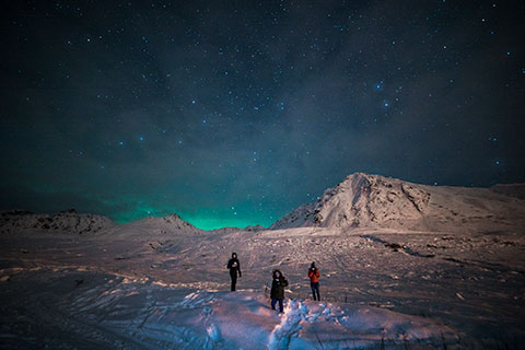three people standing on snowy mountainside with aurora glow - northern lights photo tour