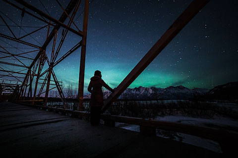 woman standing on bridge and silhouetted by auroras - northern lights photo tour