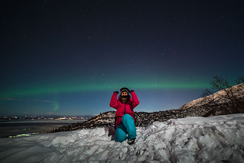 woman holding up aurora arc on mountain - northern lights photo tour