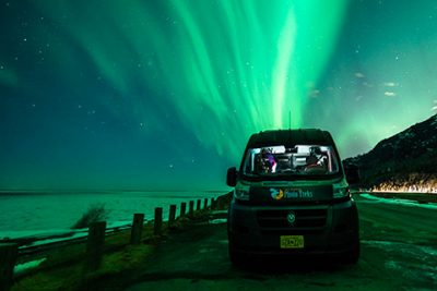 dodge promaster high top van parked in front of auroras - northern lights photo tour