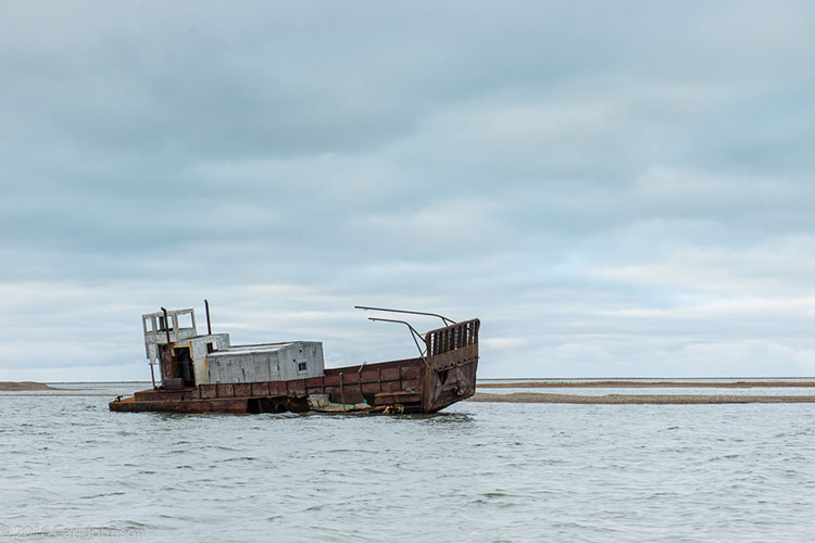 derelict boat in arctic water - polar bear photography tour