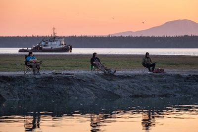 three anglers in camp chairs by ship creek at sunset on high tide - anchorage walking tour