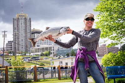 woman holding salmon with anchorage skyline behind her - anchorage walking tour