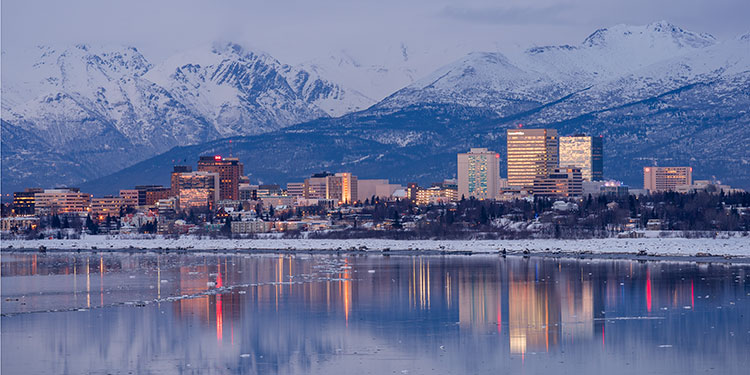 twilight view of anchorage city skyline with lights reflecting in cook inlet - helicopter photography tour