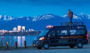 man standing on tour van photographing anchorage skyline at twilight - 10 reasons to go photo trekking