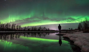 silhouette of man with northern lights in sky and reflecting on water - alaska photo tour
