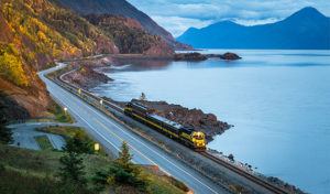 alaska railroad train traveling down turnagain arm at sunset - alaska photo tour