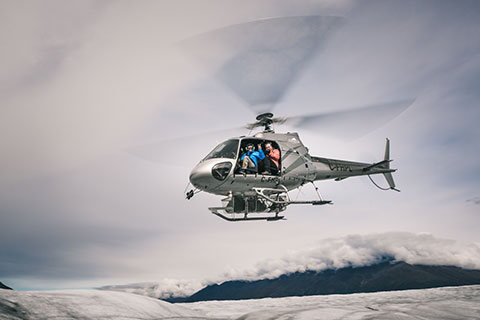 helicopter hovering with people aboard and door off - knik glacier