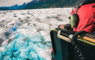 woman in red jacket photographing from helicopter with door off - knik glacier