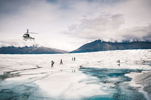 helicopter flying above group - knik glacier