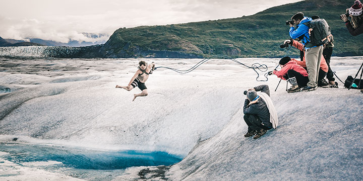 man in shorts jumping into blue ice melt pool - knik glacier
