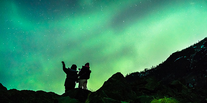 women photographers silhouetted against northern lights - private photography instruction