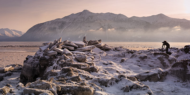 woman photographing ice flows at sunset on turnagain arm - winter photography tour