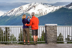 couple photographing scenery on turnagain arm with cell phone - alaska photography tours