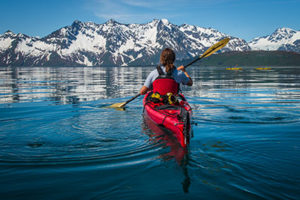 man in red kayak in front of snow mountain on sunny day in kenai fjords national park - alaska photography tours