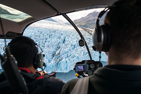 pilot and passenger looking out helicopter cockpit at knik glacier - helicopter photo tour
