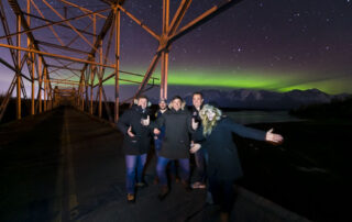 Group posing under northern lights